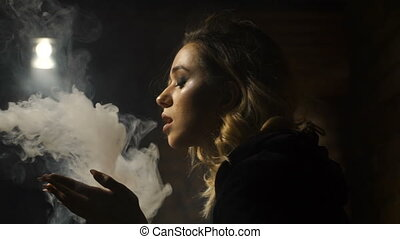 Girl emits clouds of smoke sitting in the room