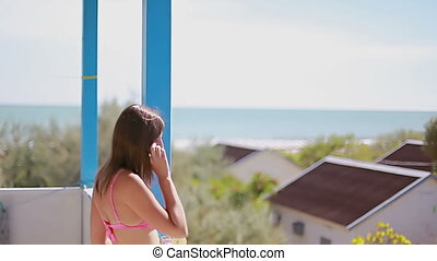 girl ends a phone conversation and walks along the summer terrace