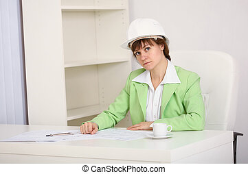 Girl engineer in white helmet on workplace at office
