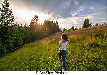 Girl enjoy pure nature. Walk over the field to meet sunset