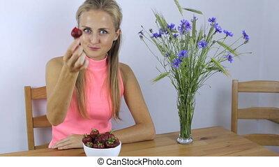 Girl enjoying a fresh strawberry