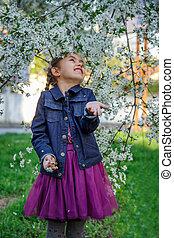 Girl enjoying flying petals among garden