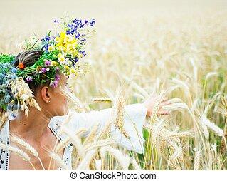 Girl enjoying in a wheat yellow field