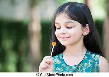Girl enjoying lolly - Closeup portrait, young girl enjoying...