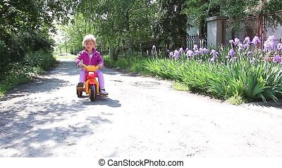 Girl enjoying riding her tricycle. - Young girl rides...
