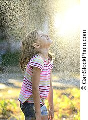 Girl enjoying the light summer rain.