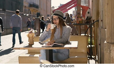 Girl Enjoys Coffee While Reading - Smiling girl, in grey...