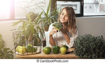 Girl Enjoys Healthy Food - Smiling girl enjoys broccoli, a...