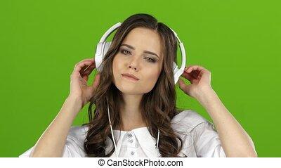 Girl enjoys music through headphones and sing along. Green screen. Close up