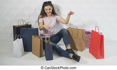 Girl Enjoys Purchases - Beautiful brunet looks into shopping...
