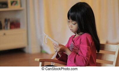 Girl Enjoys Stitching In Her Chair
