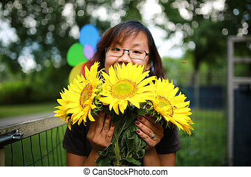 Girl enjoys sunflowers in a garden