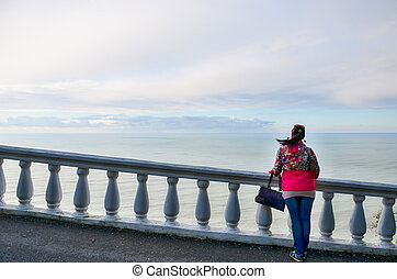 Girl enjoys views of the Black Sea in the botanical garden. Georgia, Batumi.