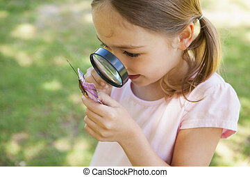 Girl examining butterfly with magnifying glass at park -...
