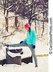 Girl exercising in winter park
