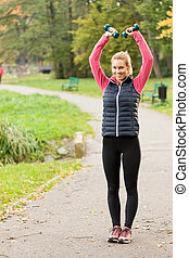 Girl exercising with dumbbells in park