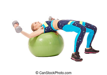 Girl exercising with dumbbells on fitness ball