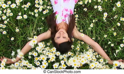 Girl falls on camomile field