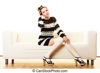 Girl fashionable dress high heels sitting on couch.