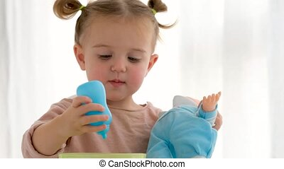 Cute little girl looking at camera and giving bottle to baby doll while playing with toy at home