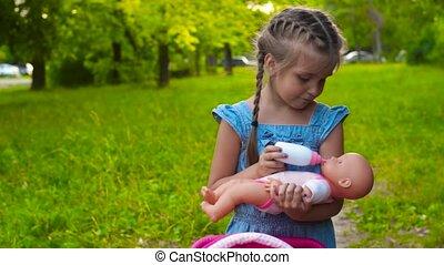 Girl feeding baby doll in park - Little girl standing in...