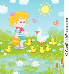 Girl feeding ducklings by a pond