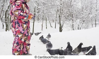 Girl feeding pigeons in a winter park