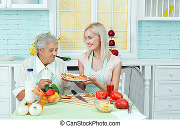 Girl feeds the grandmother with food.