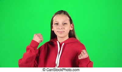 Girl feeling happy and satisfied showing yeah in studio on green background. Slow motion