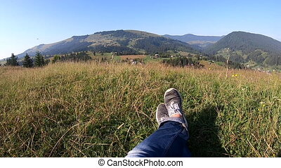 Girl feet on grass and mountain landscape scenery close-up. Nature natural background. Jeans, sneakers. Eco, ecotourism, environmentally friendly. Leisure, active rest holidays. Travel tourism trip