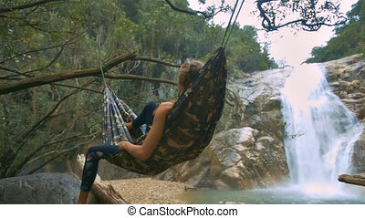 Girl Figure Lies in Soft Hammock at Waterfall back Side View...