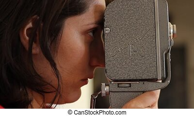 Girl Filming on 16mm - Side view of girl shooting with...