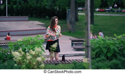 Girl films her dance on the phone. Girl in skirt and bright T-shirt dancing in the park. Brave female dancing in public