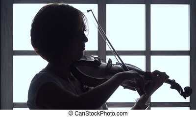 Girl fingering the strings playing on a violin against the window. Silhouette