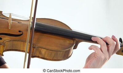 Girl fingering the strings playing the violin. Close up....
