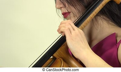 Girl fingers clamps the strings on the cello . Side view....