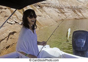 young woman fishing at Lake Powell, Utah
