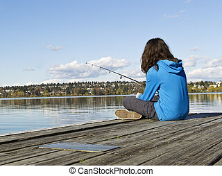 Girl fishing off Dock - Young girl fishing off dock in Lake...