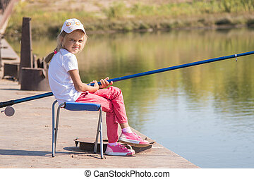 Girl fishing sitting on a chair on the bridge