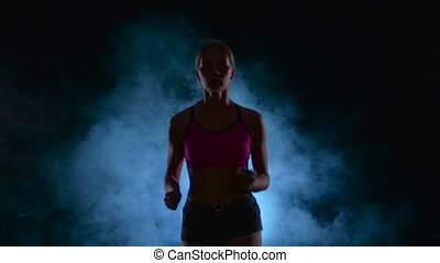 Girl fitness runs steadily. Front view. Black screen in the smoke. Silhouette. Slow motion. Close up