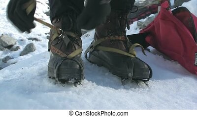 Girl fitting crampons. - Young female putting on crampons...