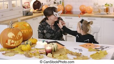 Woman in glasses sitting at kitchen table and looking at her daughter fitting white mask for Halloween party.