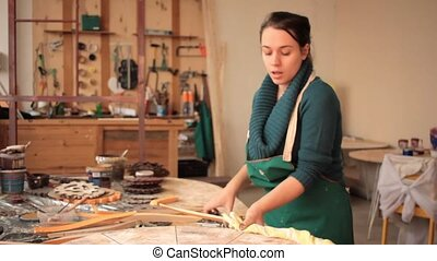 Girl fixing fabric on wooden circle - Young woman in apron...
