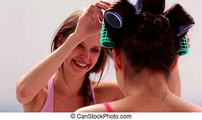 Girl fixing her friends hair roller