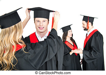 girl fixing student's graduation cap isolated on white