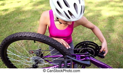 Girl fixing the chain on her bike