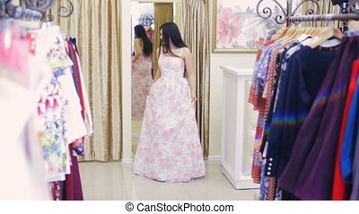 girl flaunts and looks at herself in the mirror in the clothing store
