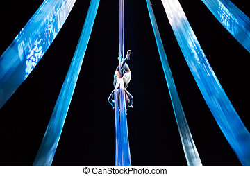 Girl flies with aerial silk in a circus stage on Devian show. Nusa Dua, Bali, Indonesia