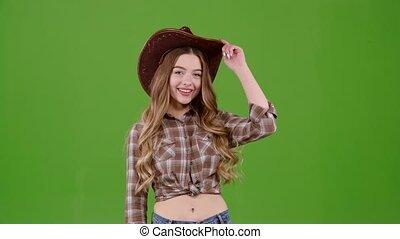 Girl flirts and winks. Green screen - Cowboy girl flirts and...