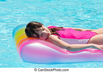 Girl floating on airbed - Young girl with her eyes closed ...